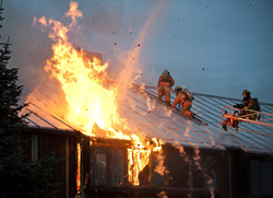 Firefighters fighting a fire on a roof