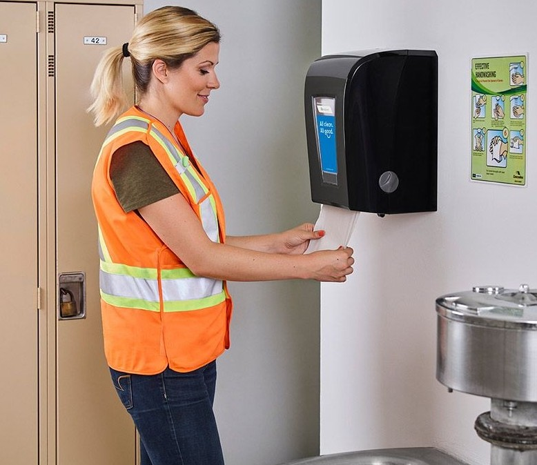 Worker taking towels from dispenser