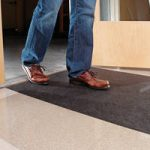 Man walking on New Pig grippy floor mat