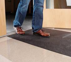 Man walking on New Pig grippy floor mat