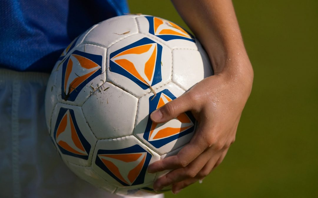 Hand holding a soccer ball against synthetic turf background