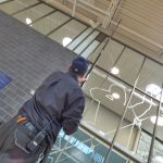 Man cleaning pipes by ceiling with long SpaceVac tool