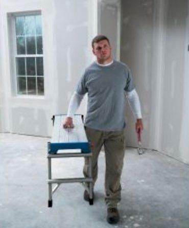 Worker carrying a work platform