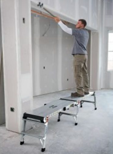 Worker smoothing drywall from 2 linked work platforms