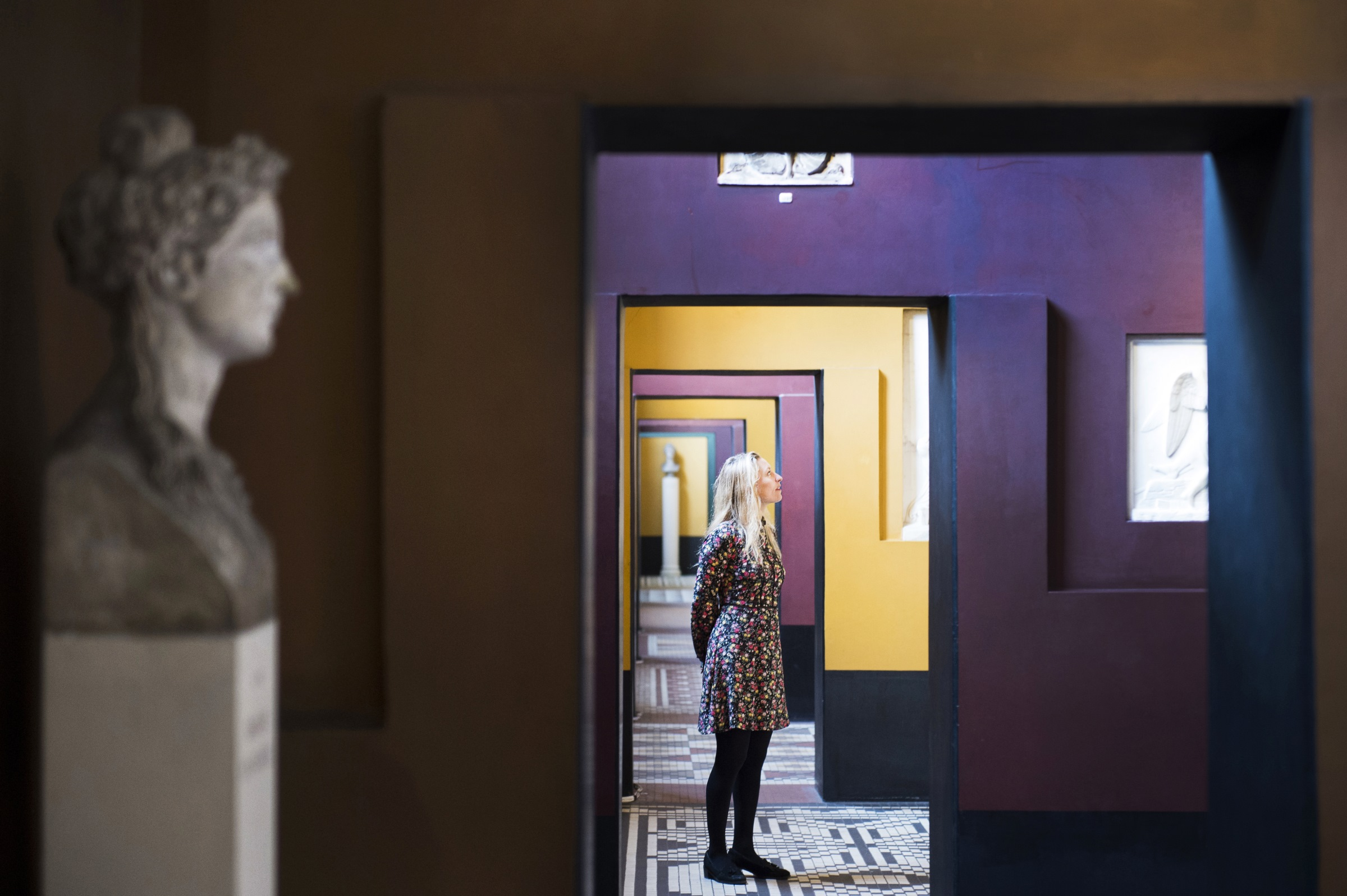 Woman framed by purple and yellow walls in Thorvaldsens Museum, Copenhagen