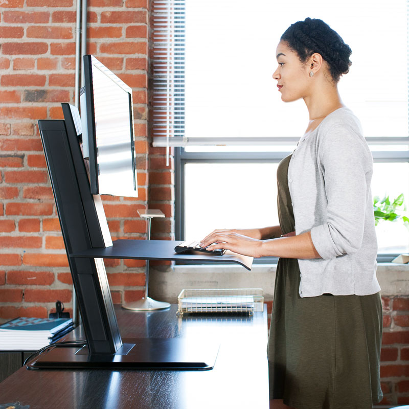 A woman using a black sit-stand workstation