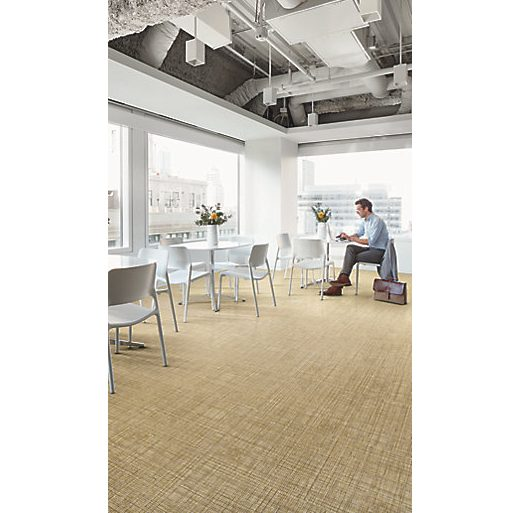 Neutral, woven-textured flooring with a man and small white tables