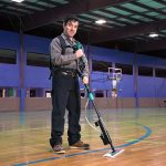 Man using Unger Excella floor-cleaning system on a gym floor