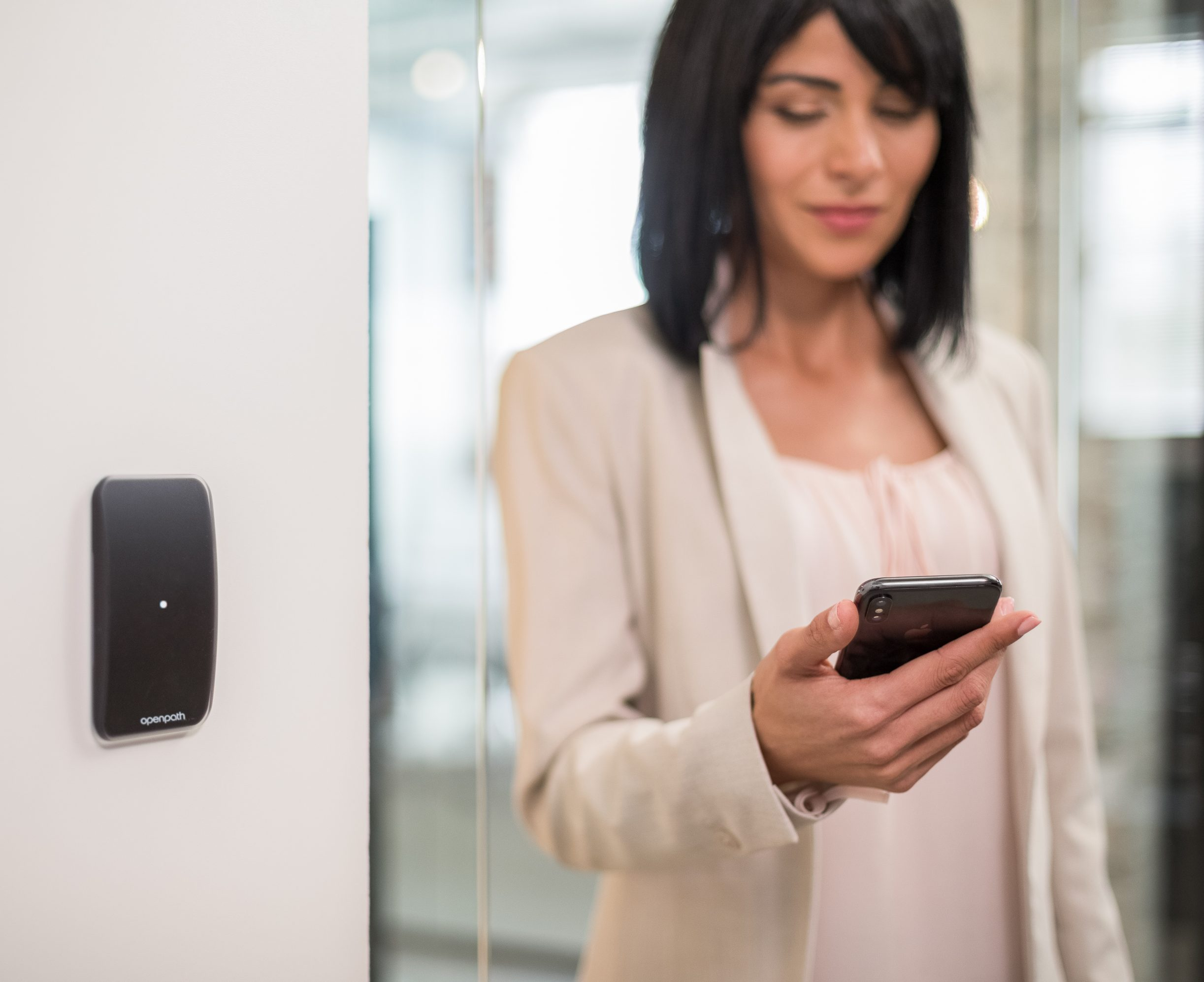 Female employee holding her phone by an Openpath reader