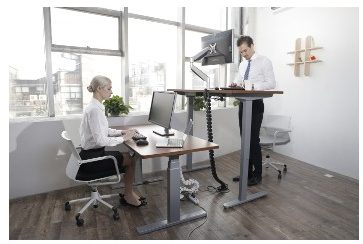 A female worker seated and male worker standing at height-adjustable desks