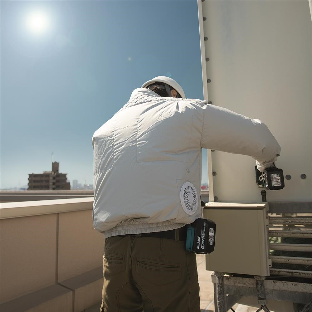Man working on equipment on roof in white fan jacket, puffed out with air