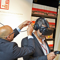 One man demonstrating virtual tech goggles to another