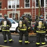 Three firefighters facing a building