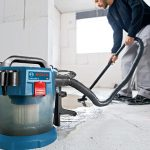 Worker using a wet/dry vacuum to clean up
