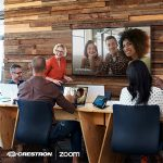 Workers around a conference table and screen