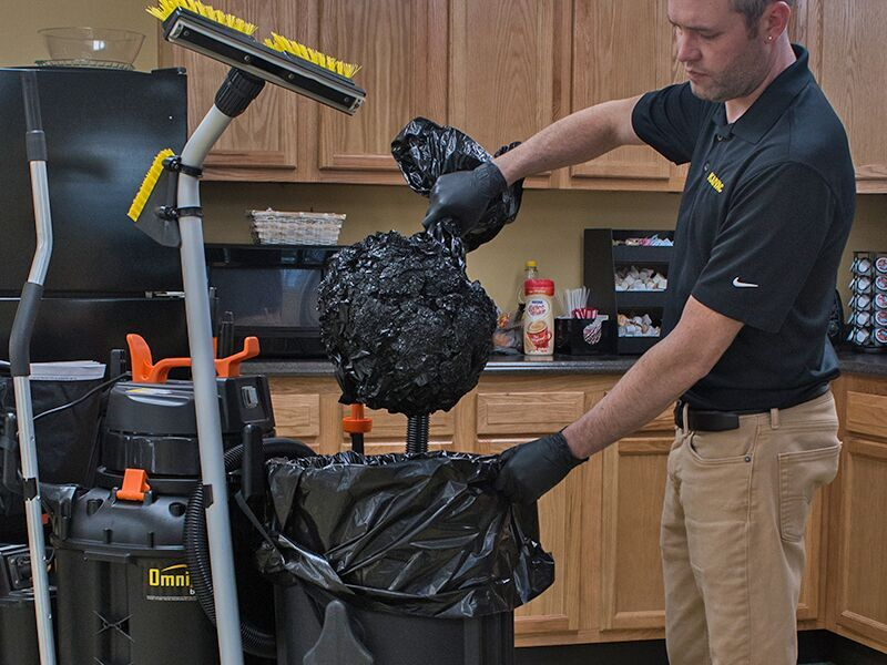 Worker vacuuming the air out a trash bag