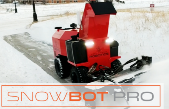 Red and black snow removal robot clearing snow from sidewalk