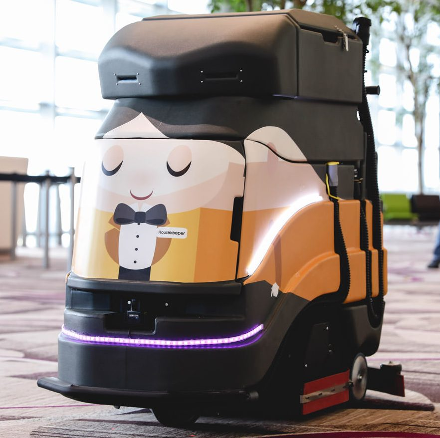Black floor-cleaning robot with friendly face and small body painted on the front