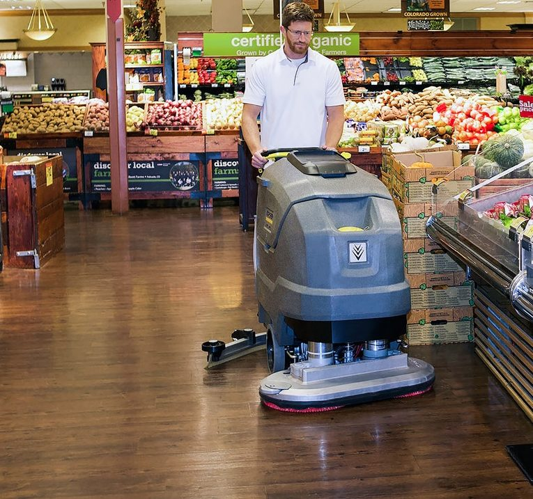 Man pushing floor scrubber in grocery store