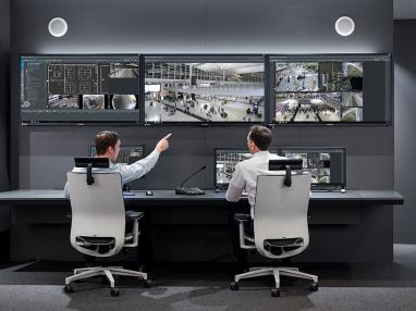 Two security professionals seated before a bank of monitors