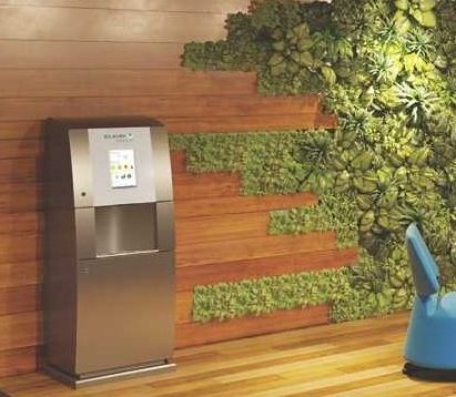 Stainless steel beverage dispenser on a wooden-plank wall with greenery