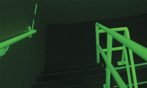 Dark stairwell with railings glowing green
