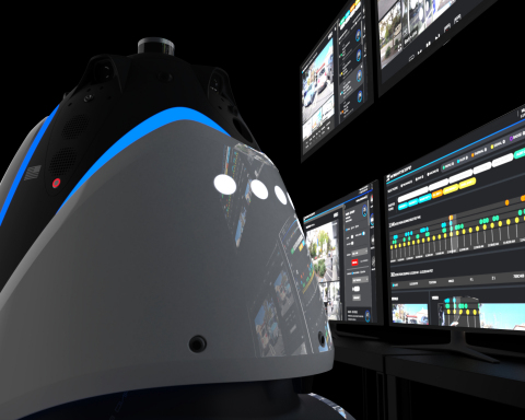Human-height bullet-shaped robot next to operations center screens
