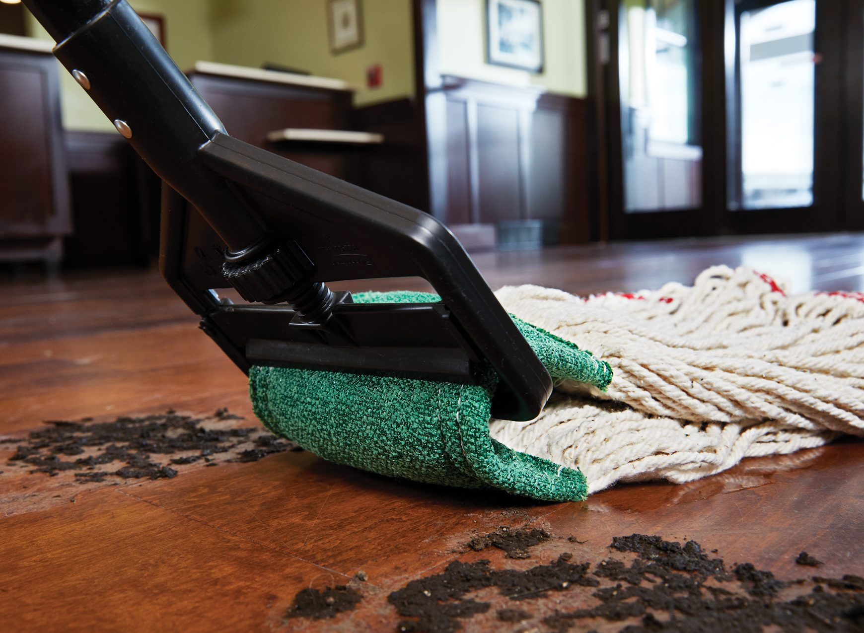 Wet mop with black handle and built-in green scrubbing pag