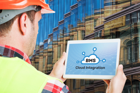 Man holding device with BuildingIQ's BMS cloud integration software in front of building