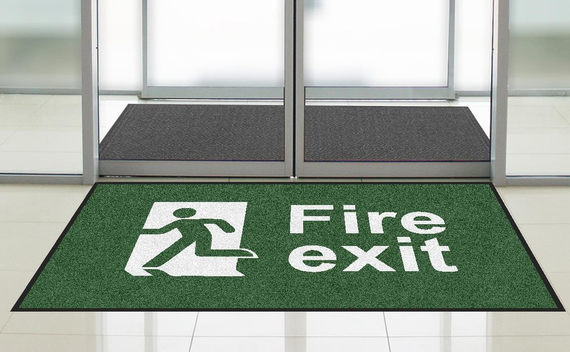 "Green floor mat from First Mats with ""Fire Exit"" safety message"