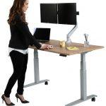 Female worker by a Howard Miller SmartMoves custom adjustable-height desk