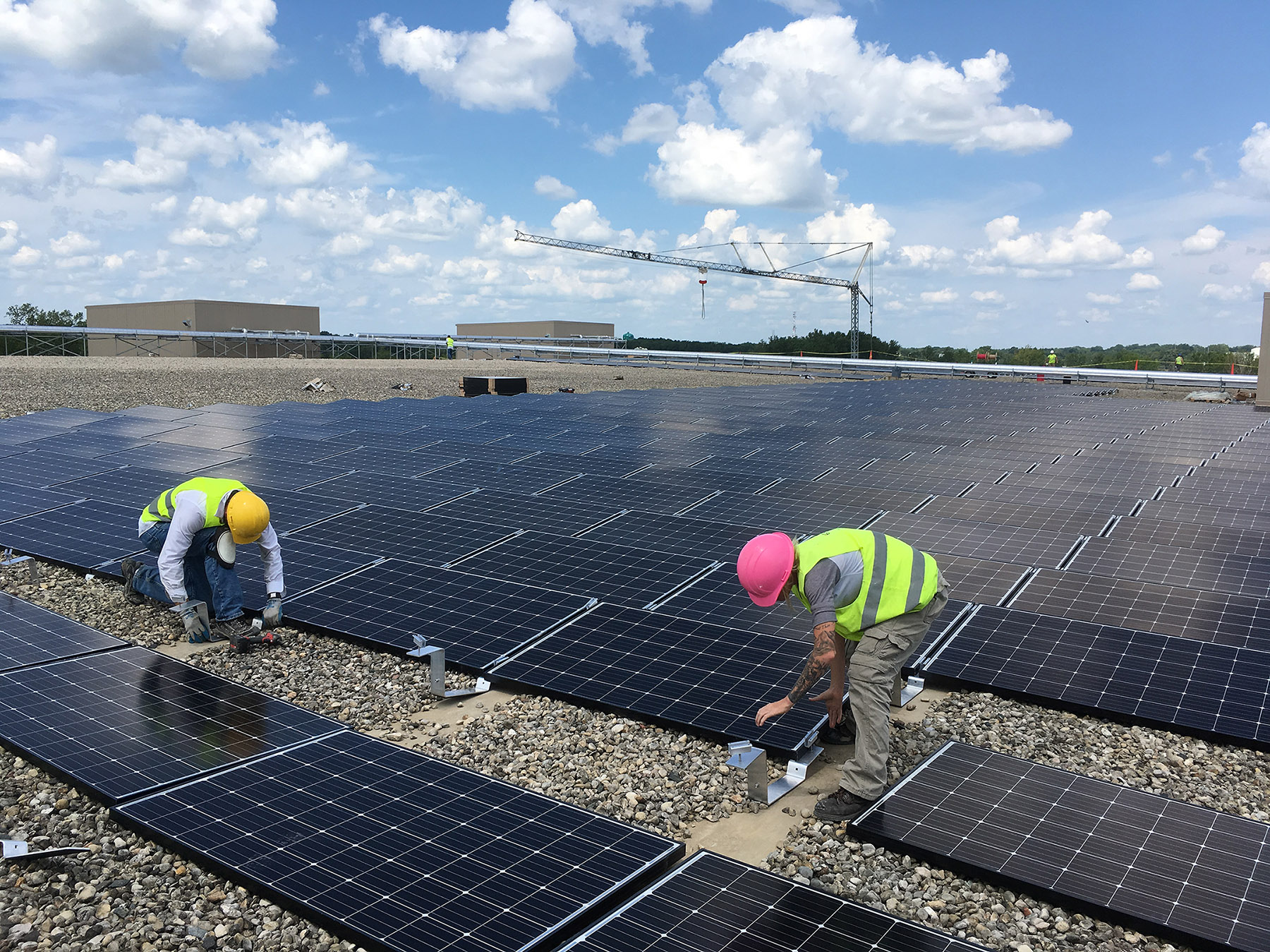 2 workers installing SunPeak solar panels on a roof