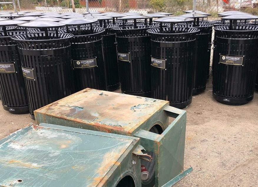 "Victor Stanley ""smart"" garbage cans labeled for Pittsburgh, with the city's old cans in the foreground"