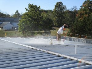 Figure 3. Installation of a liquid-applied roof coating. (From Facility Engineering Associates)