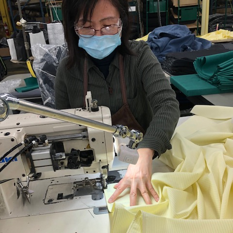 Teknion worker sewing an isolation gown